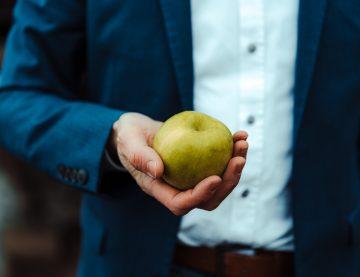 Mann hält einen grünen Apfel ins Bild